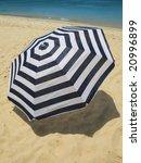 Striped umbrella on a sandy beach - stock photo