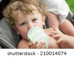baby sucking on a bottle of... | Shutterstock . vector #210014074