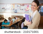 Small photo of Pretty teacher smiling at camera at back of classroom at the elementary school