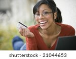 Smiling African American woman shopping on-line with credit card and laptop - stock photo