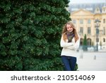 Happy young girl on a Parisian street decorated for Christmas - stock photo