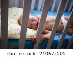 newborn sleep in crib | Shutterstock . vector #210675505