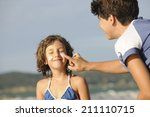 mother applying sunscreen to... | Shutterstock . vector #211110715