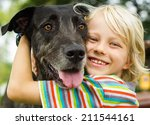 Stock photo happy young boy lovingly hugging his pet dog in the park 211544161