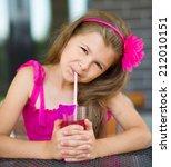 little girl is drinking cherry... | Shutterstock . vector #212010151