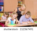 young teacher helps students of ... | Shutterstock . vector #212567491