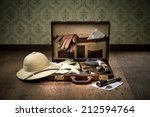 Small photo of Colonial style explorer packing with open leather briefcase, pith hat, leather gloves, maps and brass telescope.