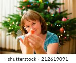 Woman decorating Christmas tree at home - stock photo