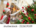 Girl with brightly decorated Christmas tree on a Parisian street - stock photo