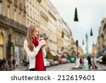 Girl with coffee on a Parisian street decorated for Christmas - stock photo