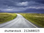 Curved asphalt road in high mountains of Iceland - stock photo