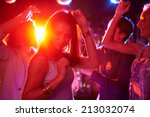 Stock photo pretty girls dancing in night club on background of guys 213032074