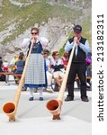 Small photo of MOUNT PILATUS - JULY 13: Unidentified people playing traditional swiss music with alphorns on July 13, 2013 on the top of Pilatus, Switzerland. Alphorn is traditional music instrument of Switzerland.