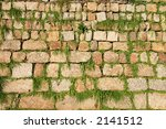 Old stone wall with grass growing through it. - stock photo