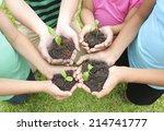 hands holding sapling in soil... | Shutterstock . vector #214741777