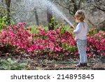cute little girl watering...   Shutterstock . vector #214895845