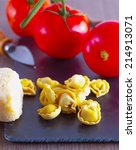Small photo of Agnolotti with cheese and tomatoes over black chopping board