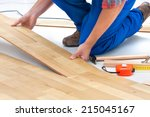 carpenter worker installing laminate flooring in the room - stock photo