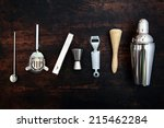 Stock photo set of bar or pub accessories with a martini cocktail shaker arranged in a neat line on a black 215462284