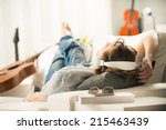 young man relaxing on sofa with ... | Shutterstock . vector #215463439
