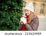 Girl drinking coffee near decorated Christmas tree - stock photo