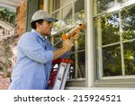 man on ladder caulking outside... | Shutterstock . vector #215924521