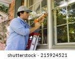man on ladder caulking outside... | Shutterstock . vector #215924521