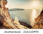 Small photo of Cliff, volcanic rocks and a traditional chapel on Santorini island, Greece. View on Caldera and Aegean sea at sunset