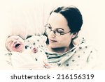 a new mother smile as she holds ... | Shutterstock . vector #216156319