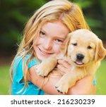 Stock photo adorable cute young girl with golden retriever puppy 216230239