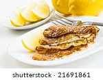 crepes with lemon and sugar on white plate - stock photo