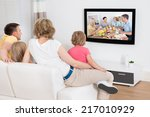 young family watching tv... | Shutterstock . vector #217010929