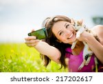 Stock photo woman taking photo with mobile phone camera of herself and her cat outdoor in nature 217202617
