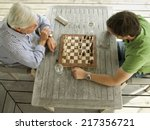 father and son playing chess | Shutterstock . vector #217356721