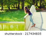 Young pensive woman in sunglasses and blue jeans standing on bridge in summer park - stock photo