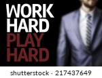 Small photo of Work Hard Play Hard written on a board with a business man on background