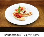Small photo of Assorted bruschetta with salmon, air-dry tomatoes or goat cheese served with the basil leaf on a round white plate on wooden table