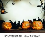 Stock photo halloween pumpkin on wooden planks cemetery grave stones on background 217534624