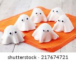 Small photo of Scary white edible Halloween ghost appetizers for party snacks or treats for young children trick-or-treating on Allhallows Eve standing ready on a colorful orange napkin