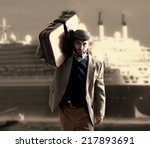 Small photo of Emigrant man with the suitcases with a transatlantic ship behind