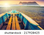 Stock photo sunrise on a mountain lake with rustic wooden boat and old foggy volcano on a skyline 217928425