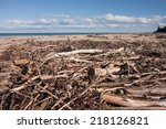 Small photo of driftwood amassed near a river mouth on a New Zealand beach