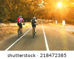 Two Cyclists Riding On Road