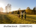 Stock photo mature couple holding hands walk retriever dog autumn sunset countryside meadow 218805241
