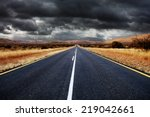 Open Tar Road With Dark Clouds