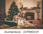 family near fireplace in... | Shutterstock . vector #219580219