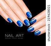 Holiday Nail Art. Luxury blue nail polish. Glitter nail stickers in silver. Manicure and makeup concept. Closeup hands isolated on black with sample text - stock photo