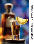 Small photo of Tequila shot and tequila bottle on bar background