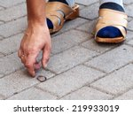 Hand And Lost Coin On Footpath...