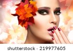 Autumn makeup and nail art trend. Fall beauty fashion girl. Professional makeup and manicure. Closeup portrait on autumnal background with falling leaves - stock photo